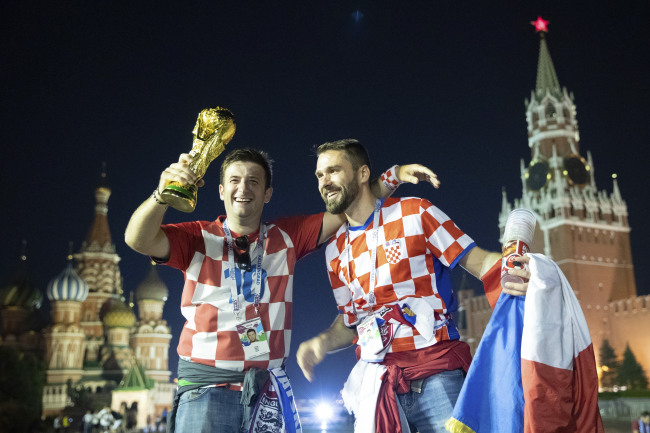 Croatia's soccer fans celebrate with a model of the World Cup trophy in Red Square as their team won the semifinal soccer match between Croatia and England during the 2018 soccer World Cup at the Luzhniki stadium in Moscow, Russia, early Thursday, July 12. (Yonhap)