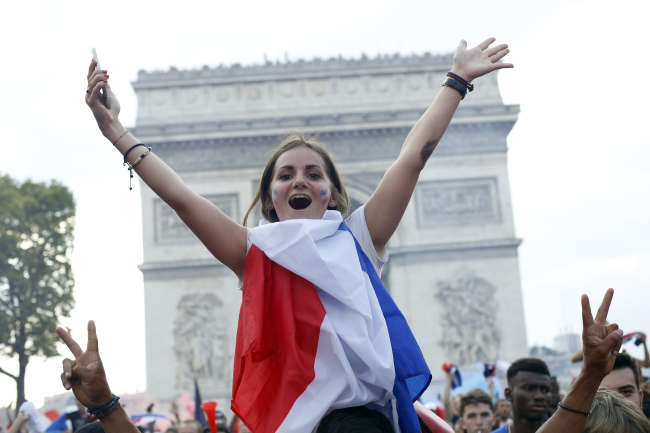 French soccer fans react on the Champs Elysees avenue with the Arc de Triomphe on background, after defeated Croatia in the final match at the 2018 soccer World Cup, in Paris, Sunday, July 15, 2018. (AP)