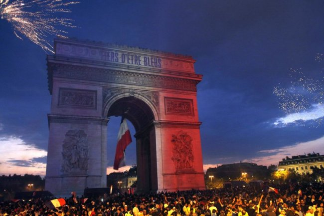 The Arc de Triomphe is illuminated with the colors of the French national flag and by fireworks set off by French soccer fans celebrating France's World Cup victory over Croatia, in Paris, France, Sunday, July 15. (AP)