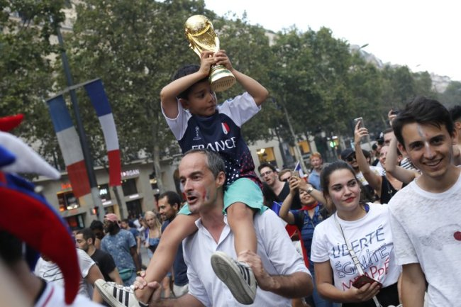 A child carries a fake Word Cup on the Champs Elysees avenue after France won the World Cup final between France and Croatia, Sunday, July 15, in Paris. (AP)