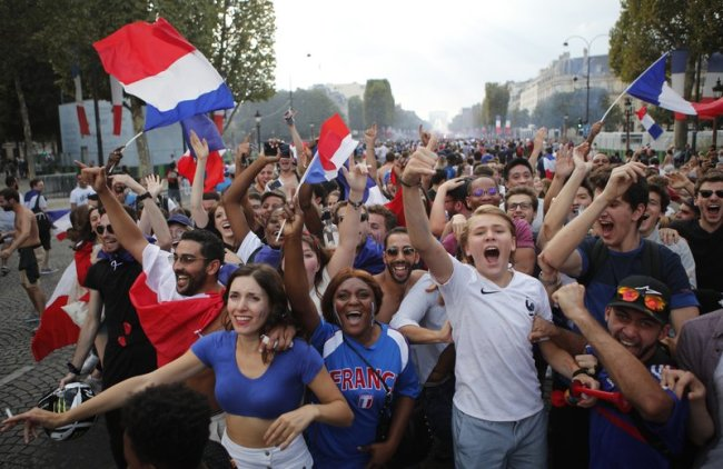 People celebrate the Champs Elysees avenue after France won the soccer World Cup final match between France and Croatia, Sunday, July 15, in Paris. (AP)