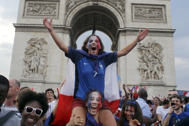 People react on the Champs Elysees avenue with the Arc de Triomphe on background, after France defeated Croatia in the final match at the 2018 soccer World Cup, in Paris, France, Sunday, July 15. (AP)