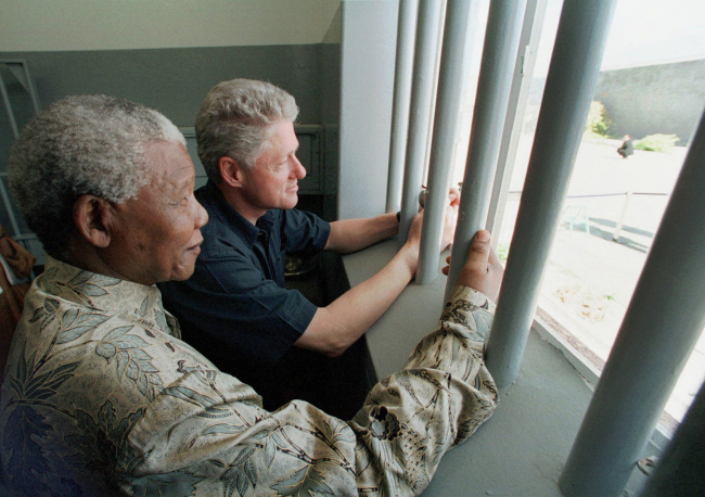 In this March 27, 1998 file photo, Nelson Mandela and former US president Bill Clinton look outside from Mandela's Robben Island prison cell, in Cape Town, South Africa. (AP/Yonhap)