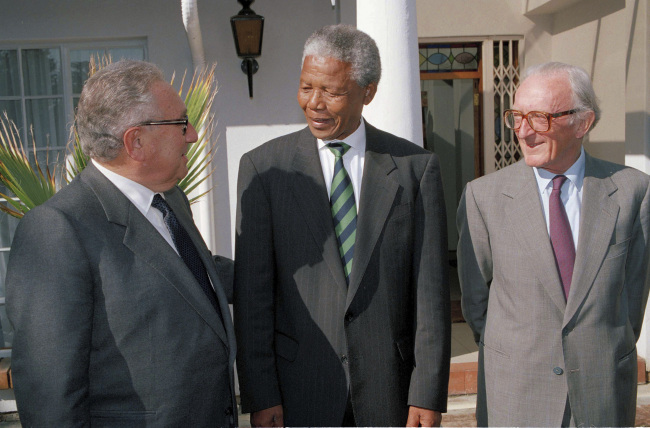 In this April 13, 1994 file photo, former US Secretary of State Henry Kissinger (left), then-African National Congress President Nelson Mandela (center) and former British Foreign Secretary Lord Carrington pose in Johannesburg, South Africa, trying to end the bloody dispute between the ANC and the Zulu Inkatha Freedom Party, who were opposed to the upcoming all-race general elections. (AP/Yonhap)