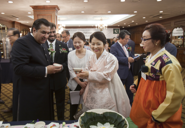Pakistani Ambassador to Korea Rahim Hayat Qureshi (left) poses with Ryoo Hyun-mi (center in white dress), chairperson of the International Food and Culture Exchange Association Korea, at the inaugural Pakistan-Korea Culture, Food and Business Forum at Imperial Palace Hotel Seoul on July 10. (Pakistani Embassy)
