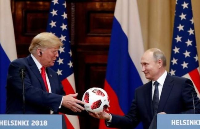 US President Donald Trump receives a football from Russian President Vladimir Putin as they hold a joint news conference after their meeting in Helsinki, Finland July 16. (Reuters)