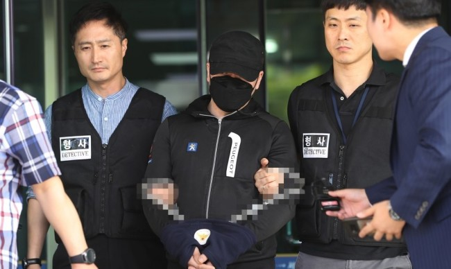 A suspect heads out of the police station in Suseo, southern Seoul, to go to the prosecutor's office on Wednesday after being arrested for installing hidden cameras and transferring the content to his computer. (Yonhap)