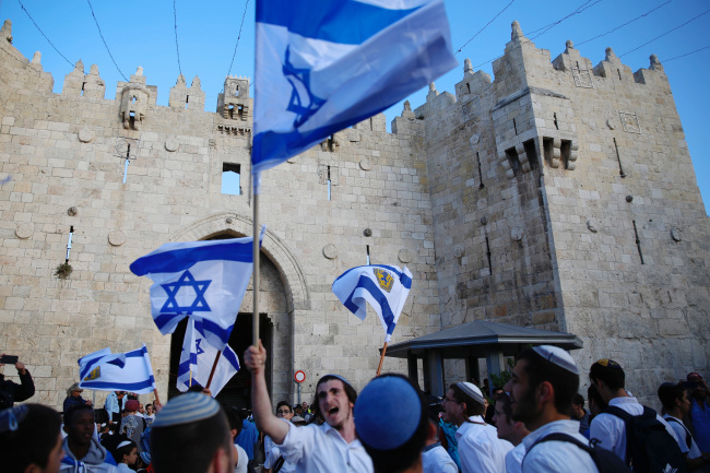 In this Sunday, May 13, 2018, file photo, Israelis wave national flags outside the Old City`s Damascus Gate, in Jerusalem. Israel`s parliament has approved a controversial piece of legislation that defines the country as the nation-state of the Jewish people. Opponents and rights groups have criticized the legislation, warning that it will sideline minorities such as the country`s Arabs. (Yonhap)