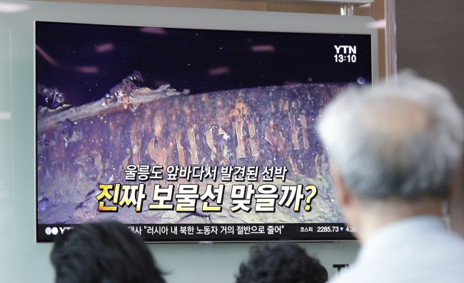 People watch a TV screen showing the news program reporting about a sunken Russian warship at the Seoul Railway Station in Seoul, South Korea, Thursday, July 19, 2018. A South Korean company`s claim to have found a sunken Russian warship has triggered investor frenzy amid unconfirmed rumors that the ship was carrying 200 tons of gold when it sank in 1905. The letters read