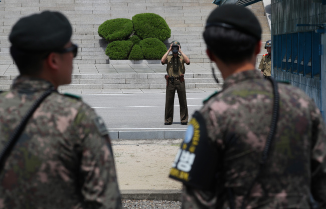 A North Korean soldier observes movement on the South Korean side of the military demarcation line in Panmunjom on July 5. (Yonhap)