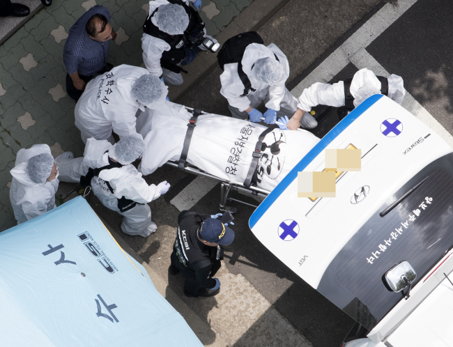 Police move the body of Roh Hoe-chan, floor leader of the minor opposition Justice Party, from an apartment complex in Seoul on Monday. (Yonhap)