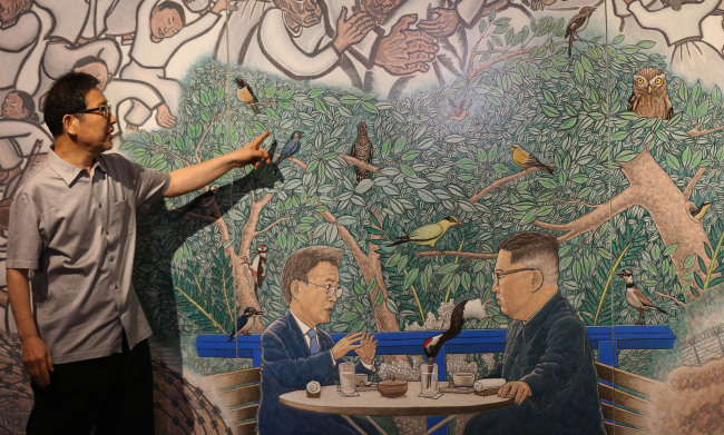 Artist Hong Sung-dam explains a painting based on the first summit between President Moon Jae-in and North Korean leader Kim Jong-un. (Yonhap)