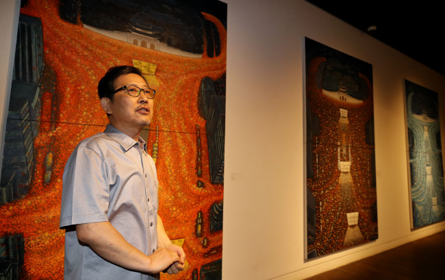 Artist Hong Sung-dam talks about his paintings based on the candlelight protests that led to the impeachment of President Park Geun-hye. (Yonhap)