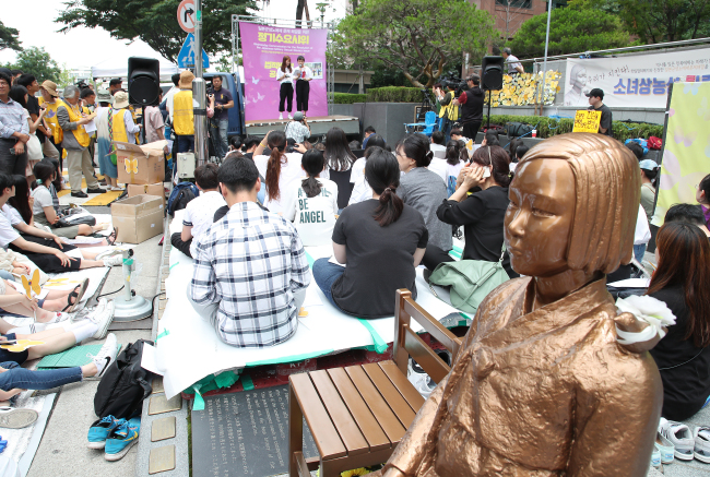 A statue (right) commemorating the victims of Japan`s sexual slavery during World War II is placed in front of the Japanese Embassy in Seoul. (Yonhap)