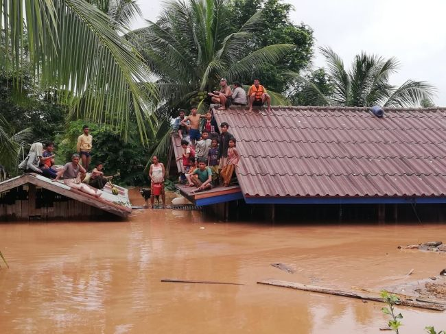 People wait for rescue operation after their houses were waterlogged by the collapse of the hydroelectric dam in Laos. (Yonhap)