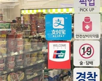 Caption: A CU store has signs to inform customers it accepts Chinese mobile payments. (BGF Retail)