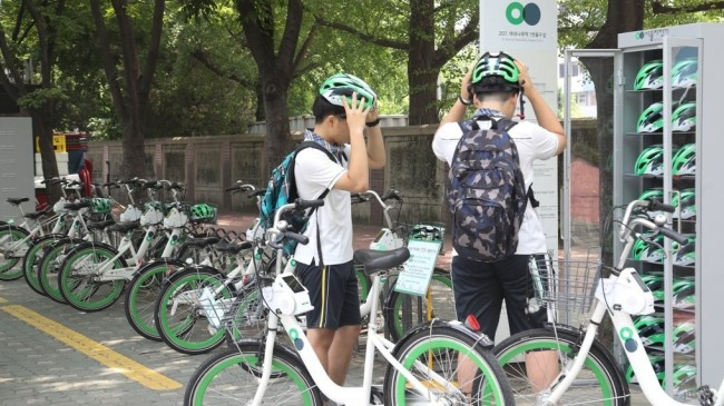Two children try on helmets provided by the Seoul Metropolitan Government during the trial helmet rental period in Yeouido, Seoul, Friday. (Yonhap)