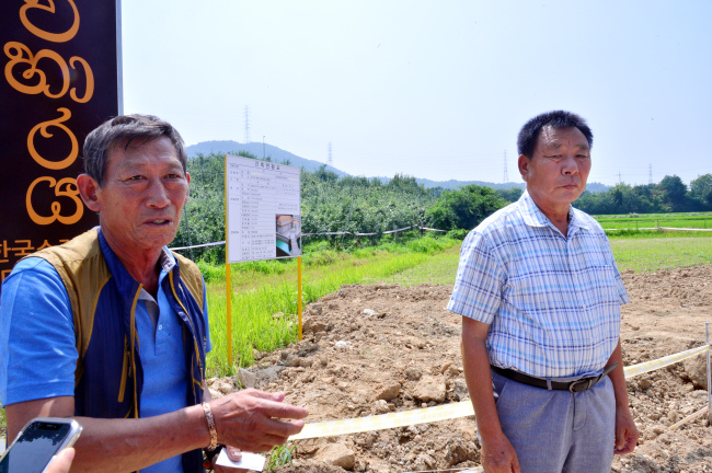 Lee Guk-hwan (right), head of the Sinjeong-ri village, and resident Kim Myung-bae stand in front of the construction site of the Korea-Sri Lanka Mahaviharaya Temple in Sinjeong-ri, Asan, South Chungcheong Province, on July 17. (Park Hyun-koo/The Korea Herald)