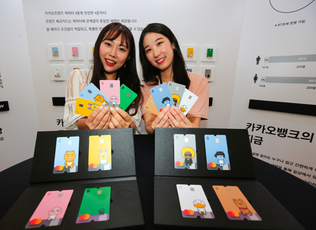 Models on Thursday present four versions of Kakao Friends debit cards that mark Kakao Bank's first anniversary. (Kakao Bank)