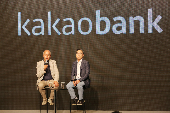Lee Yong-woo (left) and Yoon Ho-young, the co-chiefs of internet-only bank Kakao Bank, on Thursday speak in a Q&A session of a media briefing marking the company's first anniversary in business. (Kakao Bank)