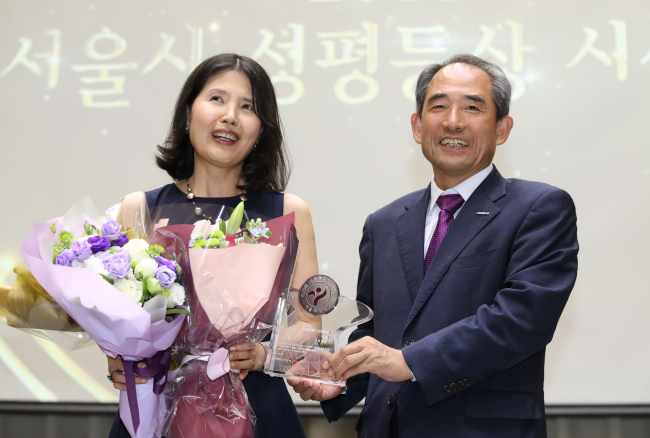 Poet Choi Young-mi (left), who has publicly accused acclaimed poet Ko Un of habitually and sexually harassing women, including herself, receives a gender equality award from the Seoul Metropolitan Government earlier this month. (Yonhap)