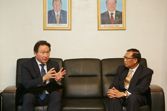 SK Group Chairman Chey Tae-won (left) talks with Laos Ambassador Khamsouay Keodalavong after delivering $10 million for relief efforts at the Laos Embassy in Hannam-dong, central Seoul. (SK Group)
