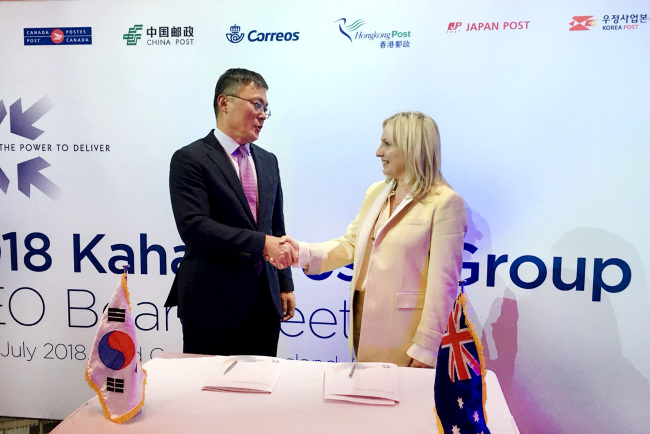 Korea Post CEO Kang Seong-ju (left) and Australia Post CEO Christine Holgate pose after signing a memorandum of understanding for business cooperation Thursday. (Korea Post)