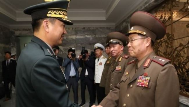 This photo, provided by Seoul`s defense ministry, shows South Korea`s top delegate Major Gen. Kim Do-gyun (L) shaking hands with his North Korean counterpart Lt. Gen. An Ik-san before starting their first general-level talks in more than 10 years at the truce village of Panmunjom on June 14. (Yonhap)