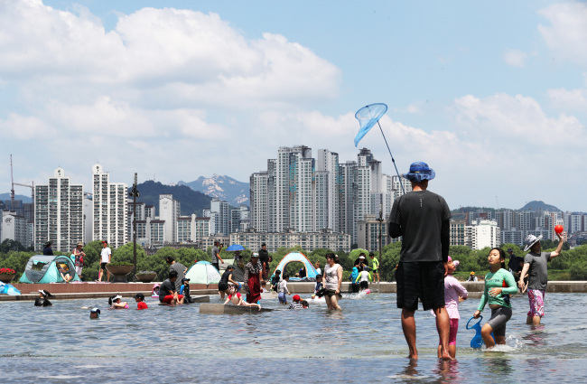 Children play with water near the Han River in Yeouido, Seoul, Sunday.