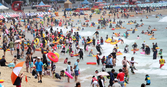 Around 450,000 people flock to beaches at Haeundae, Busan, Saturday.