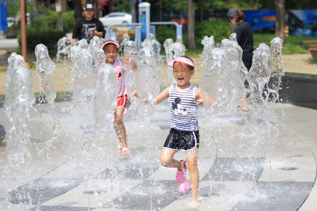 Children play at a fountain in Inje County, Gangwon Province, Monday.