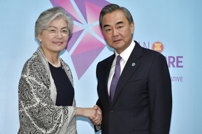 China`s Foreign Minister Wang Yi, right, and South Korea`s Foreign Minister Kang Kyung-wha pose for a photo ahead of a bilateral meeting on the sidelines of the 51st ASEAN Foreign Ministers Meeting in Singapore, Friday, Aug. 3. (AP-Yonhap)