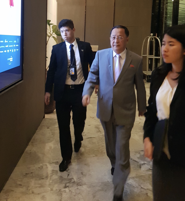 North Korean Foreign Minister Ri Yong-ho returns to his hotel in Singapore Friday night after attending bilateral talks on the sidelines of the ASEAN Regional Forum. A handful journalists, mostly Japanese, waited for Ri to arrive at his hotel. (Kim So-hyun/The Korea Herald)
