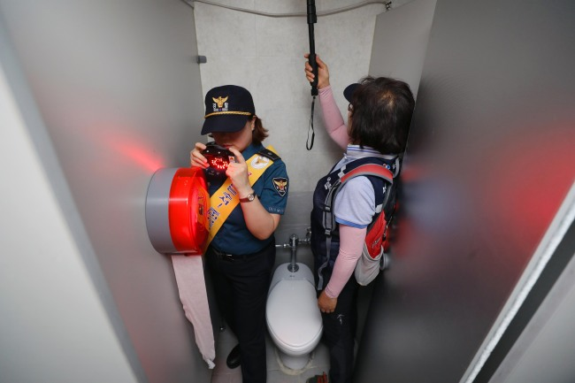 Authorities inspect a public toilet as a measure to combat spy-cam crimes in South Korea. (Yonhap)
