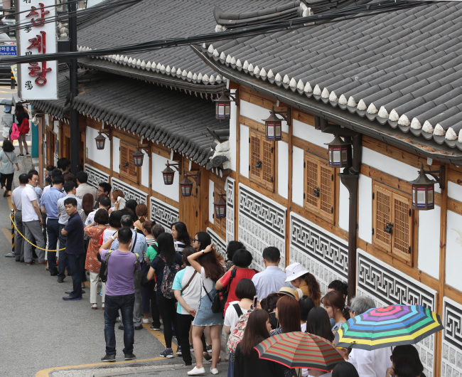 Photo caption: People line up at a well-known Samgyetang restaurant in Seoul. (Yonhap)