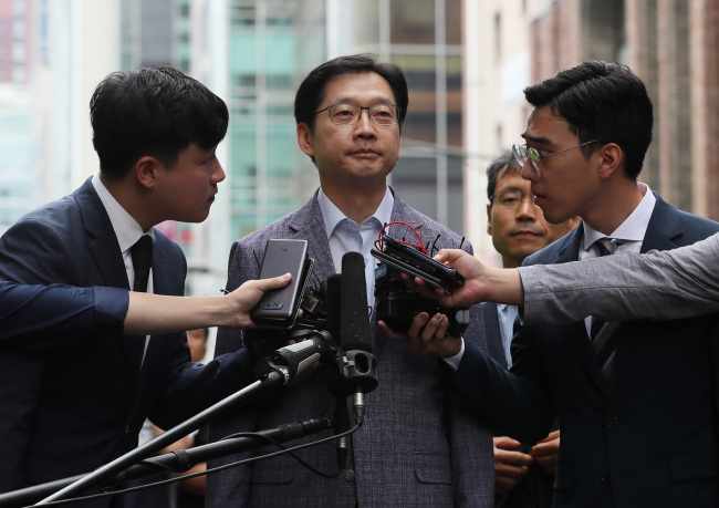 South Gyeongsang Province Gov. Kim Kyoung-soo is surrounded by reporters as he arrives at the special counsel's office in Seoul on Monday. (Yonhap)