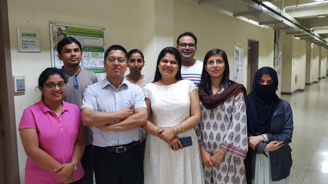 Professor Navrati Saxena (front row, center) and Abhishek Roy (front row, second from left) stand with other members of the MUSIC laboratory at Sungkyunkwan University. (Paul Kerry/The Korea Herald)