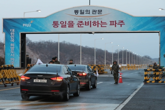 "Vehicles carrying the South Korean delegation wait in front of the Unification Bridge in Paju City on Jan. 9 on their way to Panmunjom for inter-Korean high-level talks. The gate reads ""Paju preparing for unification.""(Yonhap)"