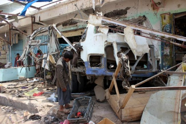 A Yemeni child stands on August 10, 2018 next to a destroyed bus, the target of a Saudi-led coalition air strike in Yemen's rebel-held Saada province. (AFP)