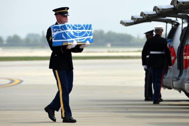 A US soldier carries a case containing the remain of American servicemember killed during the Korean War at a repatriation ceremony in Osan Air base last month. Yonhap