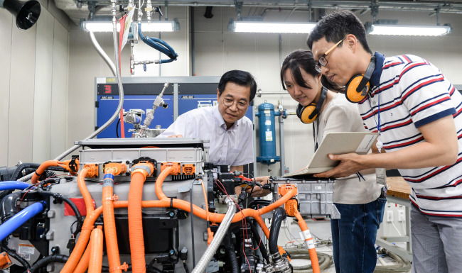 Kim Sae-hoon, vice president of Hyundai Motor's fuel cell group, and engineers look into a fuel cell stack being developed at Hyundai's Eco-technology Development Center in Yongin, Gyeonggi Province. (Hyundai Motor)