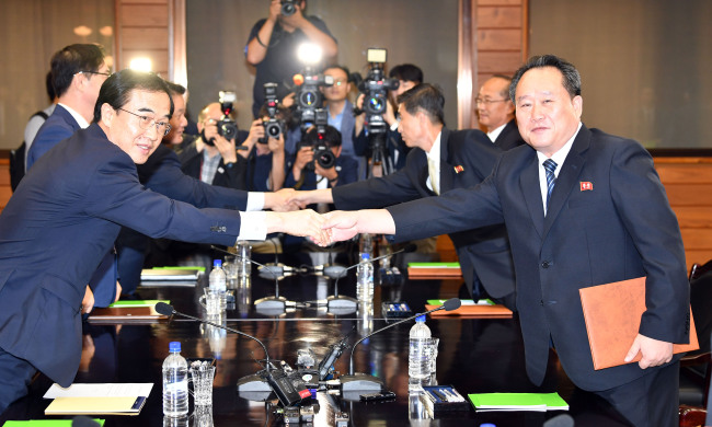 South Korean Unification Minister Cho Myoung-gyon (left) and Ri Son-gwon, chairman of the North`s Committee for the Peaceful Reunification of the Country, shake hands at Panmunjom on Monday. Joint Press Corps