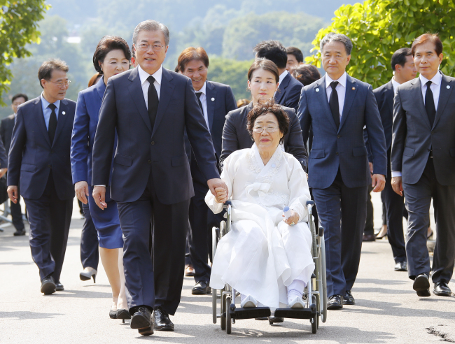 South Korean President Moon Jae-in (right) holds hands with a Korean survivor of Japan`s military sex slavery during World War II, during a special ceremony to honor the victims on Tuesday. (Yonhap)
