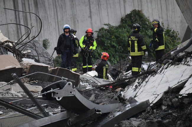 Rescues work among the debris of the collapsed Morandi highway bridge in Genoa, Tuesday, Aug. 14, 2018. Italian authorities say that about 10 vehicles were involved when the raised highway collapsed during a sudden and violent storm in the northern port city of Genoa, while private broadcaster Sky TG24 said the collapsed section was about 200-meter long (650 feet). (Yonhap)