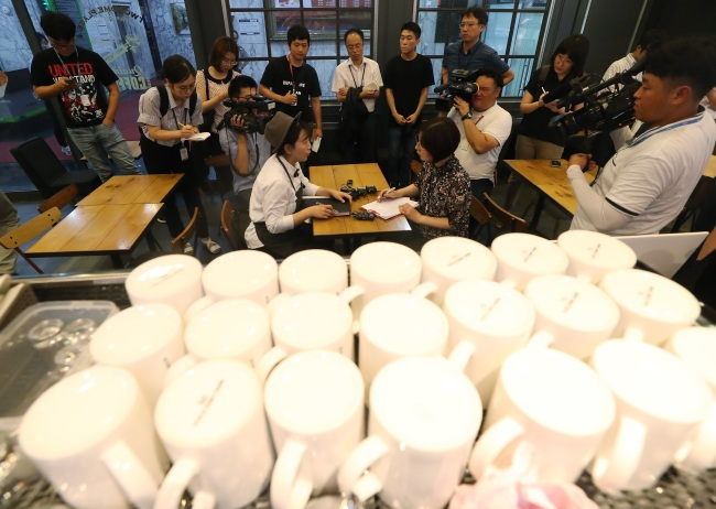 An official from the Ministry of Environment show the press how clamp-downs on coffee businesses are being done at a cafe in Seoul, on Aug.2. (Yonhap)