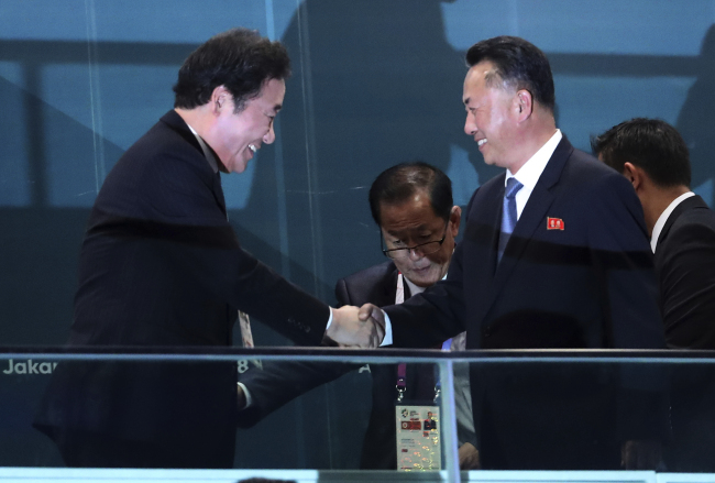 South Korean Prime Minister Lee Nak-yon (left) shakes hands with North Korean Vice Premier Ri Ryong-nam during the opening ceremony for the 18th Asian Games in the Gelora Bung Karno Stadium, Jakarta, Indonesia, Saturday. (AP-Yonhap)