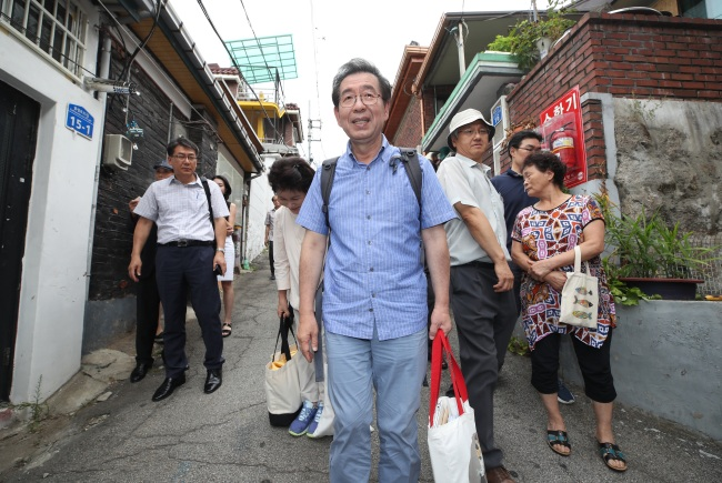 Seoul Mayor Park Won-soon (center) leaves his temporary residence -- a humble rooftop dwelling without air-conditioning -- in Samyang-dong, northern Seoul, Sunday. (Yonhap)