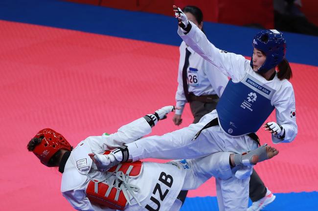 South Korea`s Kim Jan-di lands a kick on opponent Nigora Tursunkulova of Uzbekistan in the semi-final round on Monday. Yonhap