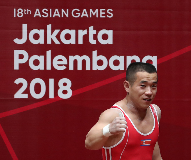 North Korean weightlifter Om Yun-chol pumps a fist after a successful lift at the Jakarta-Palembang Asian Games on Monday. Yonhap