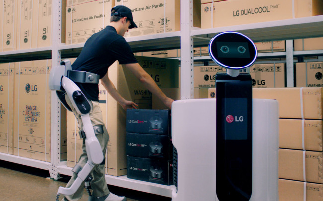 An employee wearing a CLOi SuitBot unloads boxes at a factory. (LG Electronics)